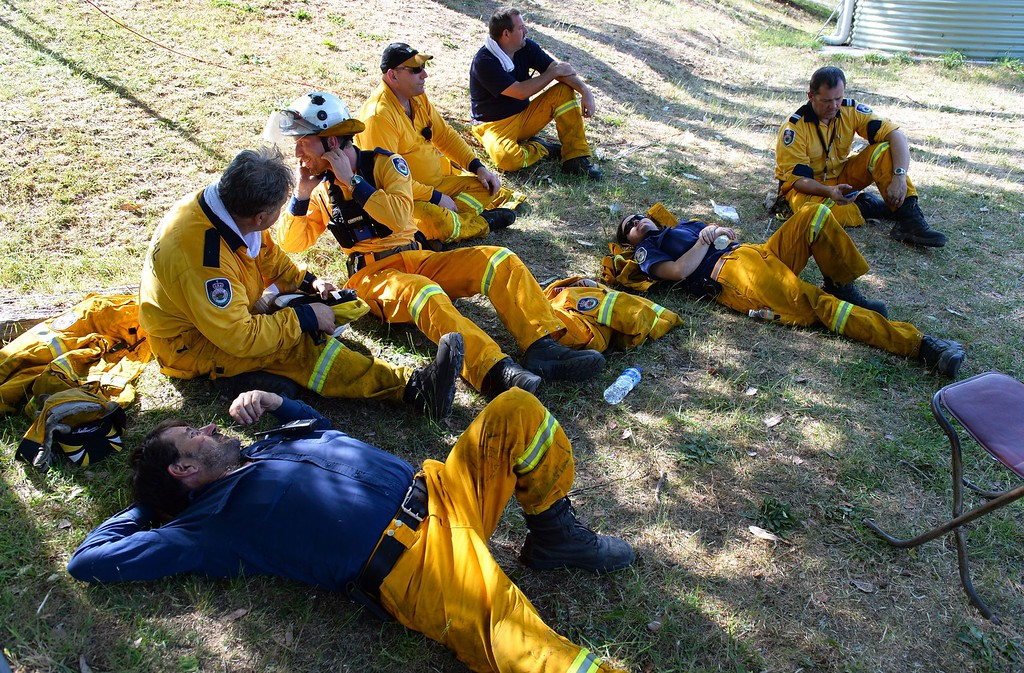 ". Firefighters take a break after back burning near Mount Victoria in the Blue Mountains on October 21, 2013, as volunteer fire brigades race to tame an enormous blaze, with officials warning it could merge with others to create a ""mega-fire\"" if weather conditions worsen.   AFP PHOTO/William WEST/AFP/Getty Images"
