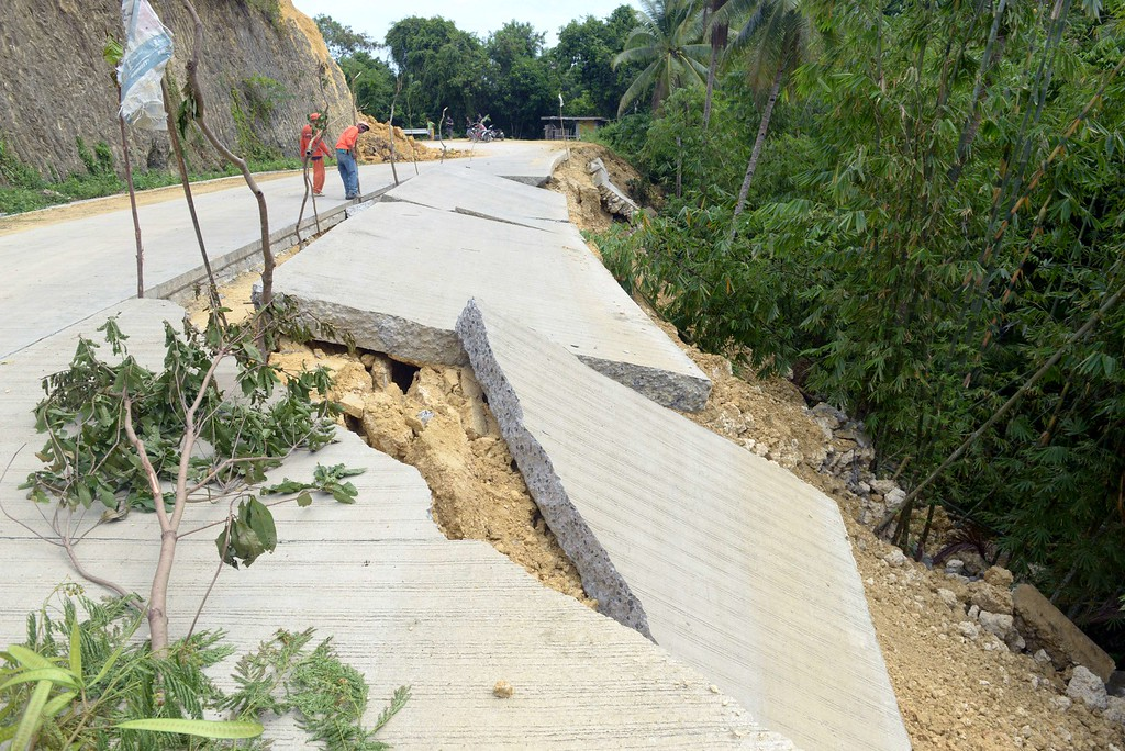 . Workers from the Department of Public Work Highway inspect a road in the Village of Cantam-is, Bohol on October 17, 2013, that was damaged during a 7.1-magnitude earthquake that hit the central Philippine island of Bohol on October 15, 2013 killing 161 people.      AFP PHOTO / Jay DIRECTO/AFP/Getty Images