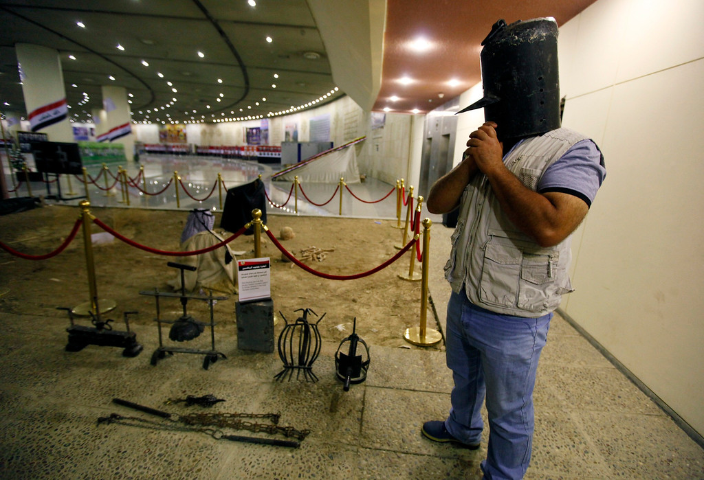 . A visitor tries on a metal mask, used as a torture device by the regime of Iraq\'s ousted leader Saddam Hussein, at an exhibition gallery at the Martyrs Monument in Baghdad May 24, 2013.    REUTERS/Thaier al-Sudani