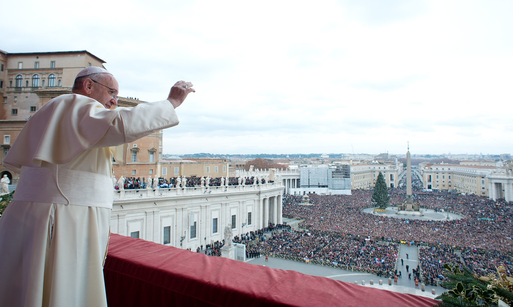 ". This handout picture released on December 25, 2013 by the Vatican press office shows Pope Francis during his traditional Christmas ""Urbi et Orbi\"" blessing from the balcony of St. Peter\'s Basilica at the Vatican.  AFP PHOTO / OSSERVATORE ROMANO"