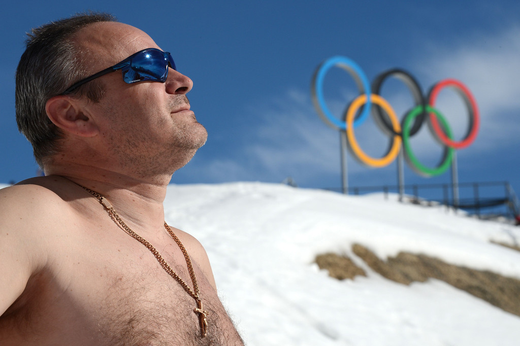 . A spectator enjoys a sunbath before the Men\'s Cross-Country Skiing 15km Classic at the Laura Cross-Country Ski and Biathlon Center during the Sochi Winter Olympics on February 14, 2014.  KIRILL KUDRYAVTSEV/AFP/Getty Images