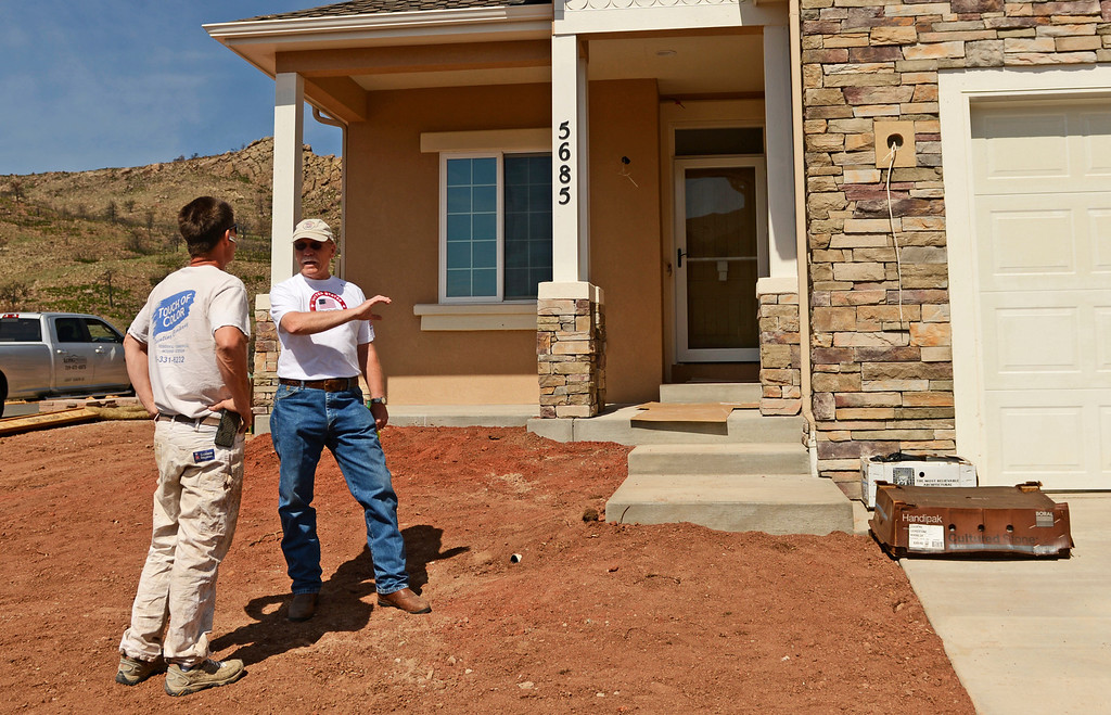 . Home owner Ralph Moreman, right, talks with his house painter outside his new home in the Mountain Shadows neighborhood in Colorado Springs, June 20, 2013. Moreman\'s home was destroyed in the Waldo Canyon fire and he will be moving into the home soon. (Photo By RJ Sangosti/The Denver Post)