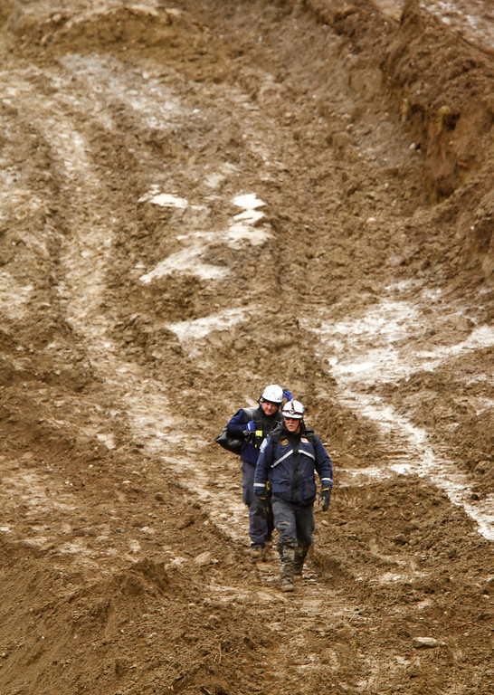 . Searchers walk on a muddy, temporary roadway being build to connect the two sides of a search area of the debris from a deadly mudslide, Thursday, March 27, 2014, in Oso, Wash.  (AP Photo/The Herald, Mark Mulligan, Pool)