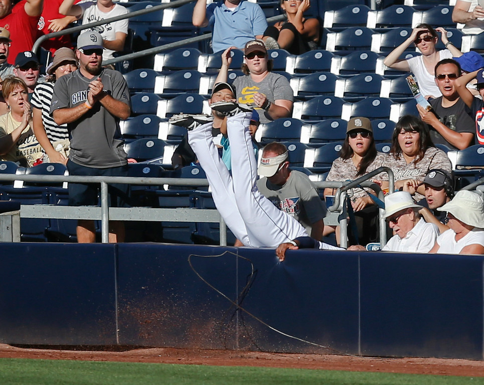 . San Diego Padres right fielder Rymer Liriano scrashes into the seats while trying to catch a pop foul hit by Colorado Rockies\' Michael McKenry as he runs into the wall in the fifth inning of a baseball game Wednesday, Aug. 13, 2014, in San Diego.  (AP Photo/Lenny Ignelzi)