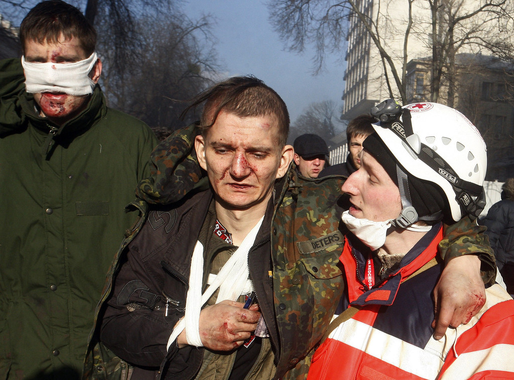 . Anti-government protesters carry a wounded man during clashes with riot police in Kiev on February 18, 2014. Ukrainian riot police approached Kiev\'s main opposition camp on February 18 after at least seven people were killed in the bloodiest day of clashes in nearly three months of protests. Opposition leader Vitali Klitschko called on women and children to quit the encampment on Kiev\'s iconic Independence Square over fears of a possible police assault. But some 25,000 protestors remained on the square after the expiry of a 6:00pm (16.00 GMT) ultimatum from security forces demanding calm be restored.   AFP PHOTO/ YURY KIRNICHNYYURY KIRNICHNY/AFP/Getty Images