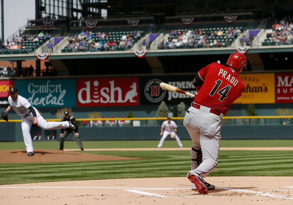 . Arizona Diamondbacks\' Martin Prado, front, doubles on a pitch from Colorado Rockies starting pitcher Brett Anderson in the first inning of a baseball game in Denver on Sunday, April 6, 2014. (AP Photo/David Zalubowski)
