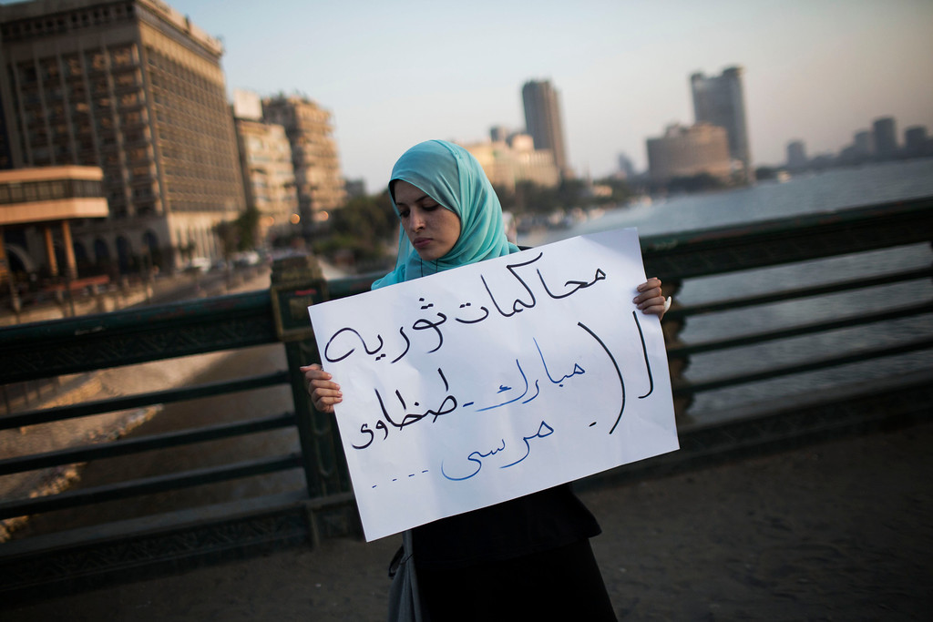 """. An Egyptian woman holds a banner that reads in Arabic \""""Revolutionary trial for Mubarak, Tantaui and Morsi during a protest against the release of former Egypt\'s dictator Hosni Mubarak in Qasr Al-Nil bridge in downtown Cairo, Egypt, Thursday, Aug. 22, 2013. (AP Photo/Manu Brabo)"""
