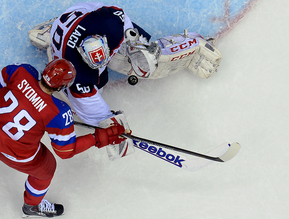 . Slovakia\'s goalkeeper Jan Laco challenges Russia\'s Alexander Syomin (L) during the Men\'s Ice Hockey Group A match between Russia and Slovakia at the Bolshoy Ice Dome in Sochi during the Sochi Winter Olympics on February 16, 2014.  ALEXANDER NEMENOV/AFP/Getty Images