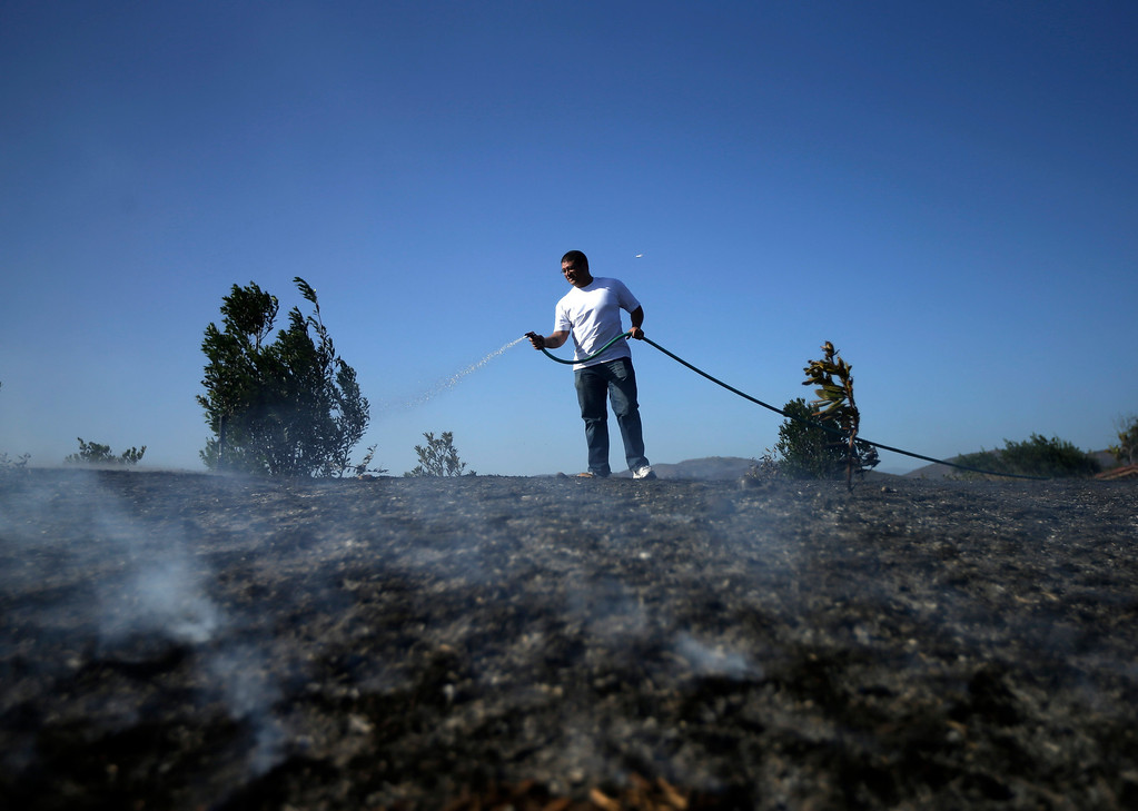 . Anthony Novom waters down smoldering vegetation surrounding his home in the Rancho Santa Fe neighborhood during a wildfire Tuesday, May 13, 2014, in San Diego. Wildfires pushed by gusty winds chewed through canyons parched by California\'s drought, prompting evacuation orders for more than 20,000 homes on the outskirts of San Diego and another 1,200 homes and businesses in Santa Barbara County 250 miles to the north.  (AP Photo)