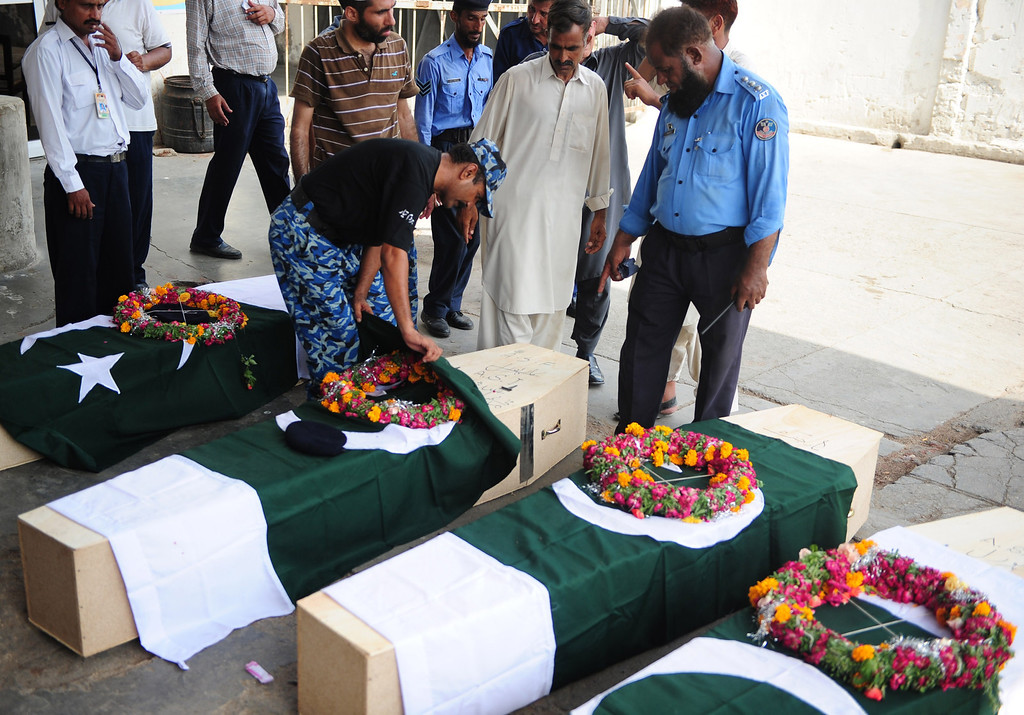 . Pakistani Airport Security Force (ASF) personnel and family members gather alongside the coffins of colleagues killed in an assault by militants on Karachi airport, and to be flown to Islamabad, at the airport in Karachi on June 9, 2014.   AFP PHOTO/Asif HASSAN/AFP/Getty Images