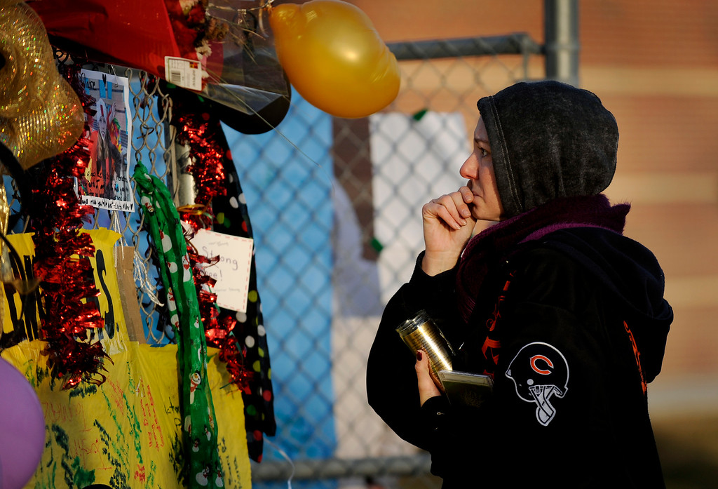 . Danielle Arno, a graduate of Arapahoe High School who knew Claire Davis, mourns the death of the 17-year-old shooting victim on Dec. 22 near a memorial along a fence outside AHS in Centennial. Photo by Jamie Cotten, Special to The Denver Post