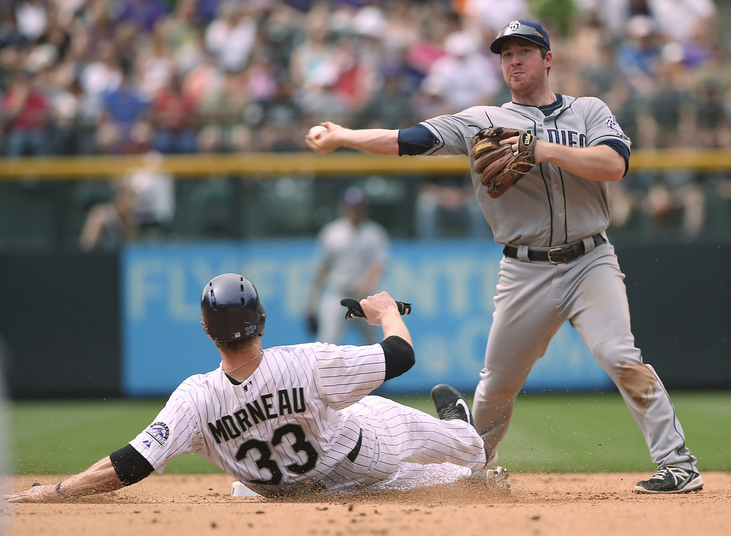 . San Diego Padres second baseman Jedd Gyorko, back, turns to throw to first base after forcing out Colorado Rockies\' Justin Morneau at second base in the fourth inning of a baseball game in Denver on Sunday, May 18, 2014. Colorado\'s Wilin Rosario beat out the throw to first base. (AP Photo/David Zalubowski)