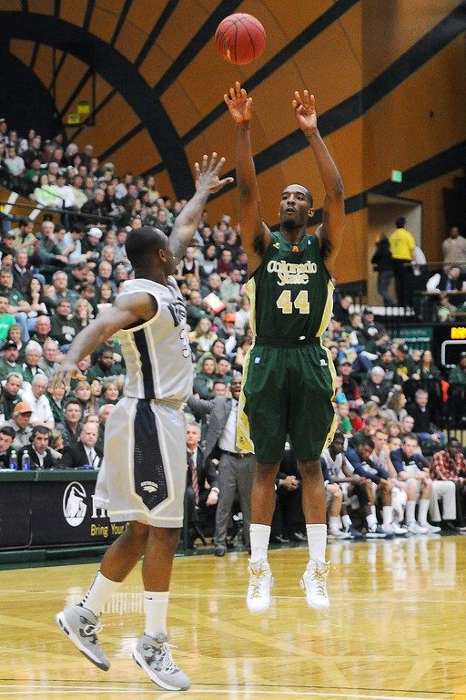 . Colorado State University senior Greg Smith, right, attempts a 3-pointer over Nevada defender Malik Story in the second half of their game on Saturday, March 9, 2013 at Moby Arena. Steve Stoner, Loveland Reporter-Herald