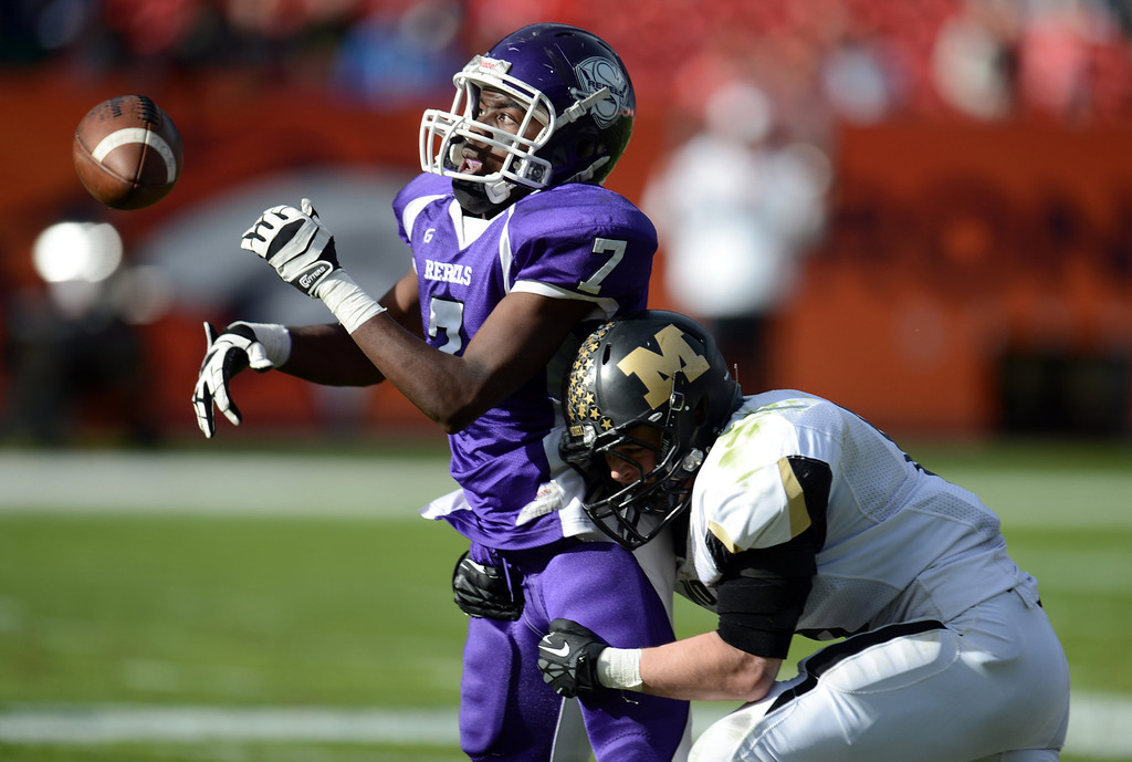 . Denver South WR Orlando Mosley, left, misses a catch as he is tackled by Monarch\'s Geoff Clary during 4A State Championship game at Sports Authority Field at Mile High on Saturday, Dec. 1, 2012. Monarch won 17-14. Hyoung Chang, The Denver Post