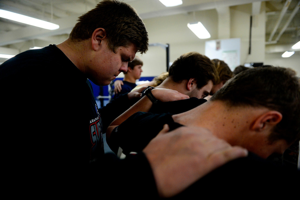 . Valor Christian left guard Ryan Cummings prays with teammates following a lift. Valor Christian\'s offensive line has dominated opponents this season. (Photo by AAron Ontiveroz/The Denver Post)