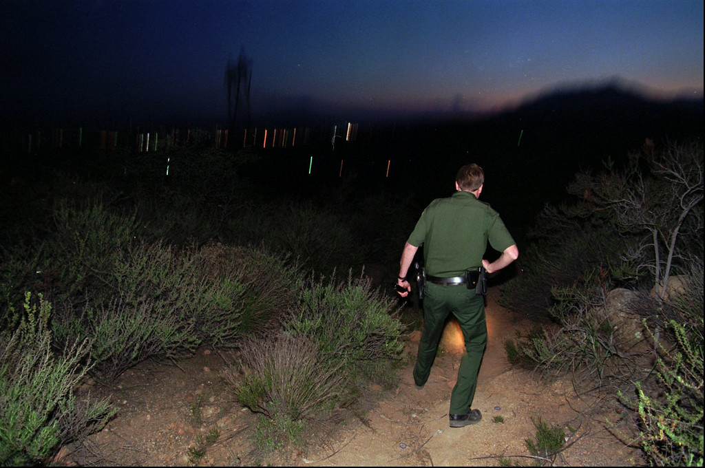 . United States Border Patrol Agent Dean Eppen searches for the footprints of a group of illegal immigrants in Campo, Calif. near the U.S.-Mexico border, Wednesday, April 3, 1996. In the backround are the lights of Tecate, Mexico.  Eppen, who works alone, often follows large groups of illegal immigrants through the rugged area in eastern San Diego county. (AP Photo/Denis Poroy)