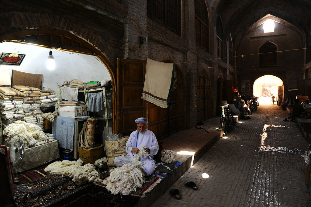 . In this picture taken on June 3, 2014, an Afghan shopkeeper examines silk threads at his shop in part of Herat\'s old city. AFP PHOTO/Aref  Karimi/AFP/Getty Images