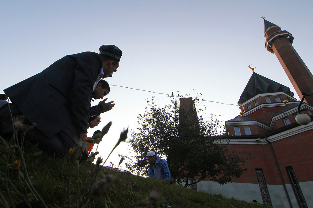 . Russian Muslims pray outside a Mosque at Poklonnaya Hill in Moscow ,Thursday, Aug. 8, 2013. Muslims in Russia celebrate the Eid al-Fitr that marks the end of the holy fasting month of Ramadan. (AP Photo/Denis Tyrin)