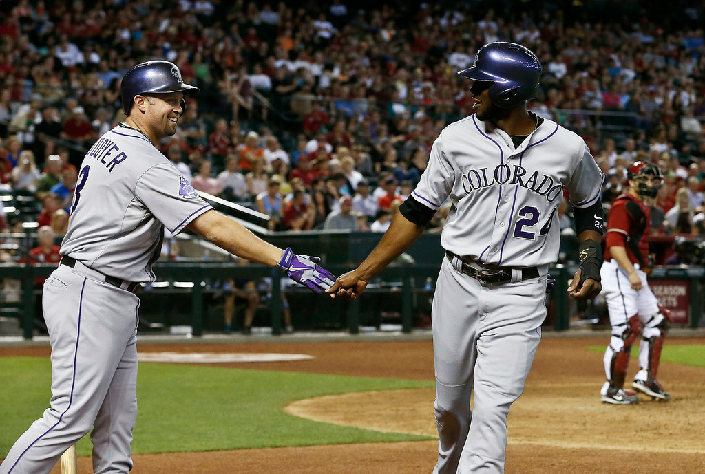 . Colorado Rockies\' Michael Cuddyer, left, smiles as he shakes hands with teammate Dexter Fowler after Fowler scores a run against the Arizona Diamondbacks during the sixth inning of a baseball game on Sunday, April 28, 2013, in Phoenix. (AP Photo/Ross D. Franklin)