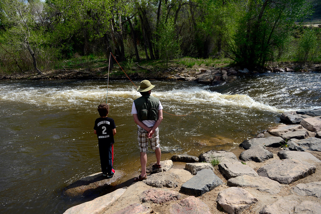 . Scott Copanas stands with his son, Nicholas, 9, as he fishes during Golden Games at the Clear Creek Whitewater Park. (Photo by AAron Ontiveroz/The Denver Post)