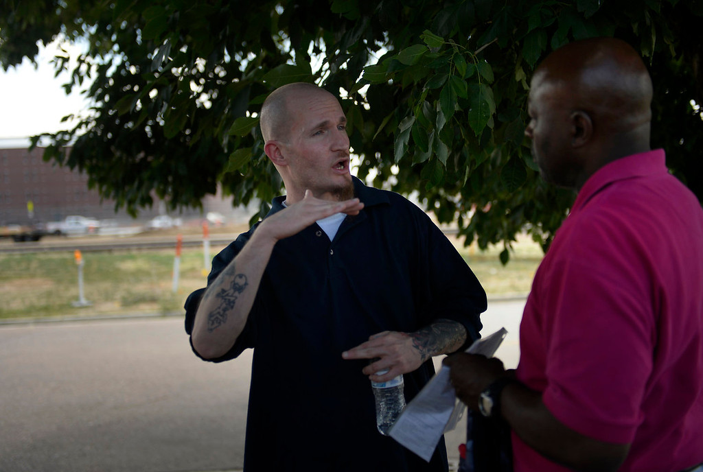 . Parolee 35 year old Thomas Vescio talks with Warren Holloway the Director of Colorado Community Church, Jail Ministry after being released on parole from the Colorado Department of Corrections on July 08, 2013 in Commerce City, Colorado. Holloway can be the inmates\' first contact with the outside world after their prison time. He offers a backpack with personal care products, a Bible, a resource sheet and bus tokens among other items to help the men in their first days of freedom.  (Photo By Joe Amon/The Denver Post)