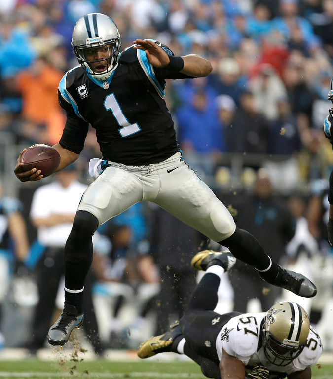 . Carolina Panthers\' Cam Newton (1) hurdles New Orleans Saints\' David Hawthorne (57) in the second half of an NFL football game in Charlotte, N.C., Sunday, Dec. 22, 2013. The Panthers won 17-13. (AP Photo/Bob Leverone)