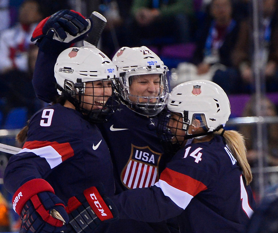 . epa04083234 Kacey Bellamy (C) of USA celebrates a goal with teammate Megan Bozek (L) and Brianna Decker (R) against Sweden in the first period during the semi final match between USA and Sweden at the Shayba Arena in the women\'s Ice Hockey tournament at the Sochi 2014 Olympic Games, Sochi, Russia, 17 February 2014.  EPA/LARRY W. SMITH