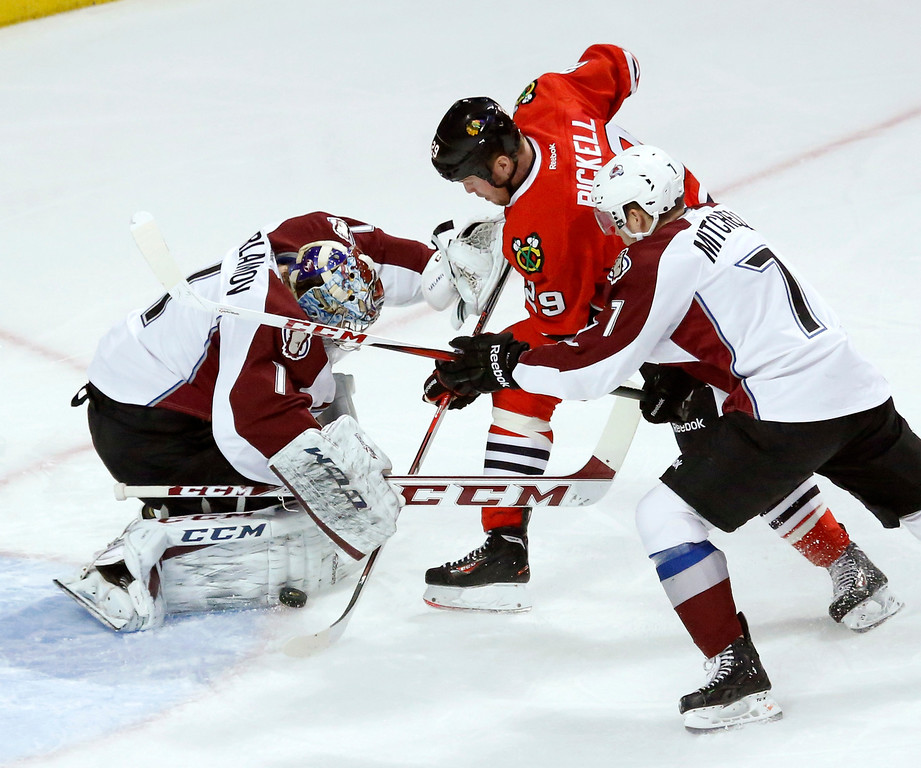 . Colorado Avalanche goalie Semyon Varlamov (1) makes a save on a shot by Chicago Blackhawks left wing Bryan Bickell (29) as John Mitchell (7) also defends during the first period of an NHL hockey game, Tuesday, Jan. 14, 2014, in Chicago. (AP Photo/Charles Rex Arbogast)