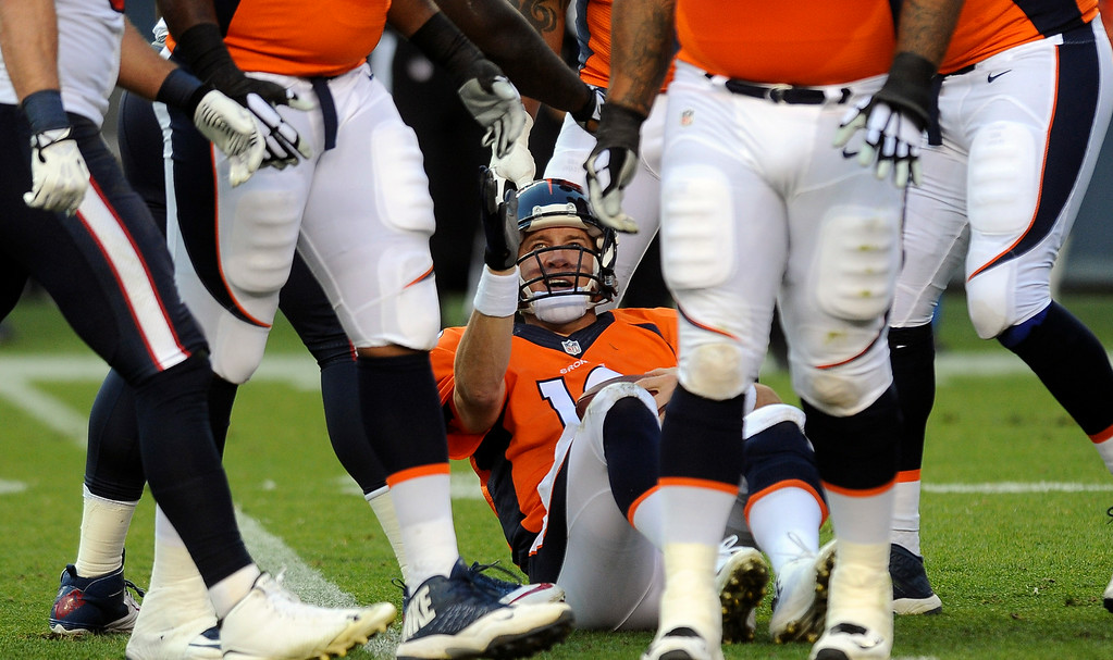 . DENVER, CO - AUGUST 23: Peyton Manning gets sacked on the first drive of the preseason game against the Houston Texans at Sports Authority Field at Mile High on Saturday, August 23, 2014 in Denver, Colorado.  (Photo by Steve Nehf/The Denver Post)