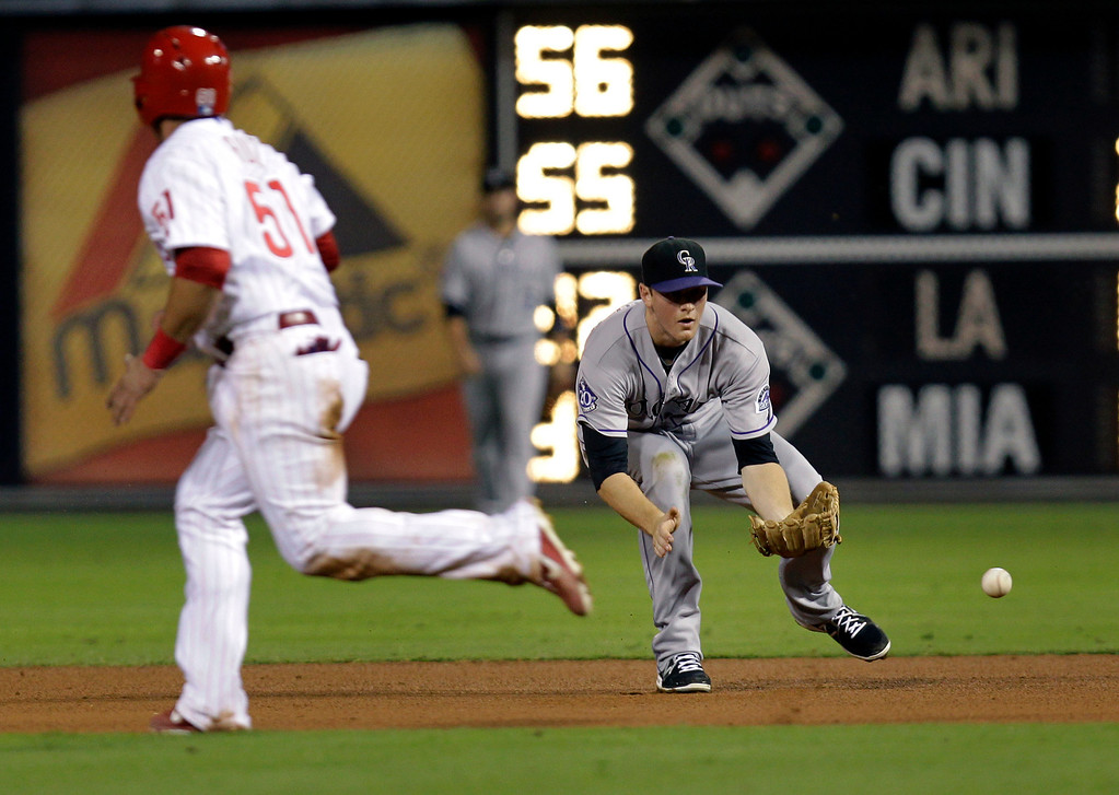 . Colorado Rockies\' DJ LeMahieu fields a hit by Philadelphia Phillies\' Cody Asche as Carlos Ruiz, left, runs to second in the fourth inning during a baseball game, Thursday, Aug. 22, 2013, in Philadelphia. Ruiz was tagged out on the fielder\'s choice. (AP Photo/Laurence Kesterson)