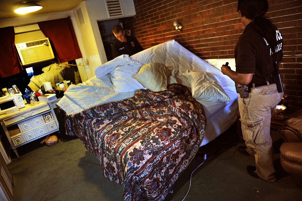 . ENGLEWOOD, CO - AUGUST 7:    Parole Officers Ryan Burch, left, and Crystal Thomas, right, upend a parolee\'s bed while doing a thorough search of his room at the Riviera Motel in Aurora, CO on August 7, 2013.  The parolee was arrested for violating parole when the officers found drug paraphernalia on his person.   Any kind of parole violations such as drugs, drug paraphernalia, pornography etc. are considered a violation of parole. The visits are unscheduled and the parolees never know when a parole officer is going to stop by their place of residence.  The officer is allowed to completely search their apartment looking for any parole violations.  The Riviera Motel is a place where many parolees go when they get out on parole.  They are given two weeks worth of vouchers to stay at hotels such as these along Colfax Ave.  (Photo by Helen H. Richardson/The Denver Post)