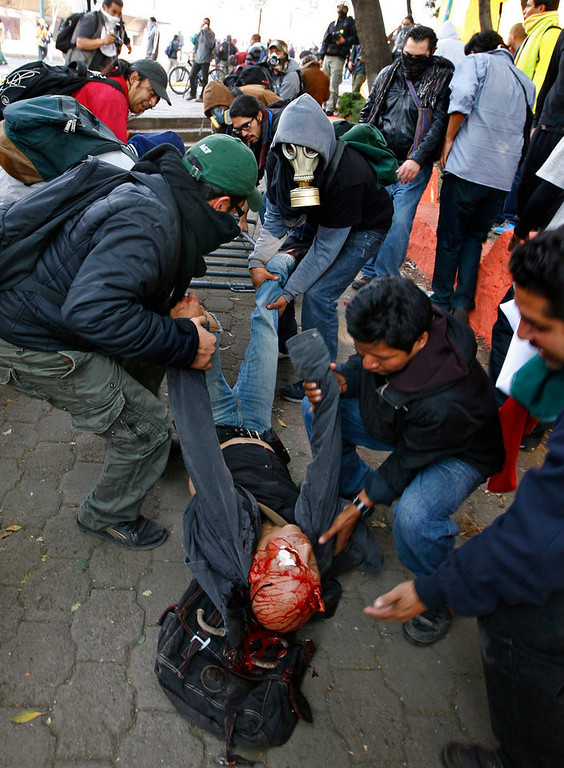 . A seriously injured man is carried by demonstrators after he was hit with a tear gas canister shot by riot police during protests against new Mexican President Enrique Pena Nieto\'s rule, outside the National Congress, in Mexico City, Saturday, Dec. 1, 2012.   Pena Nieto took the oath of office as Mexico\'s new president on Saturday amid protests inside and outside the congressional chamber where he swore to protect the constitution and laws of the land. At least two protesters were injured, one gravely. (AP Photo/Marco Ugarte)