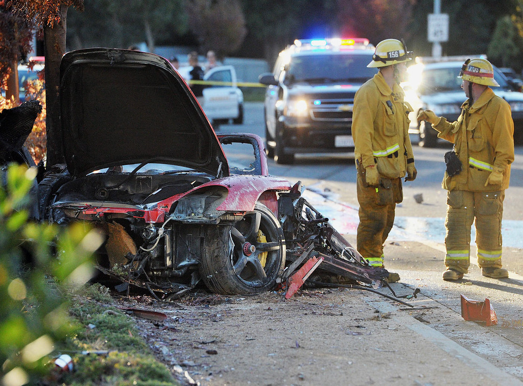 """. First responders gather evidence near the wreckage of a Porsche sports car that crashed into a light pole on Hercules Street near Kelly Johnson Parkway in Valencia on Saturday, Nov. 30, 2013. A publicist for actor Paul Walker says the star of the \""""Fast & Furious\"""" movie series has died in a car crash north of Los Angeles. He was 40. Ame Van Iden says Walker died Saturday afternoon. No further details were released. (AP Photo/The Santa Clarita Valley Signal, Dan Watson)"""
