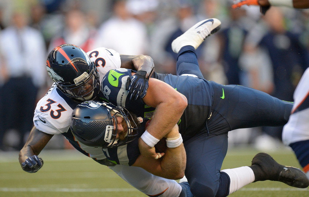 . SEATTLE, WA. - AUGUST 17: Seattle Seahawks tight end Sean McGrath (84) gets wrapped up by Denver Broncos safety Duke Ihenacho (33) after a gain during the first quarter August 17, 2013 at Century Link Field. (Photo By John Leyba/The Denver Post)