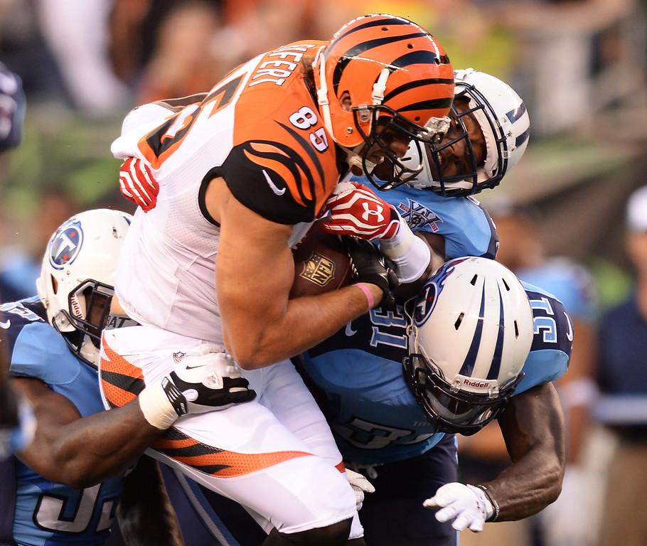 . CINCINNATI, OH - AUGUST 17:  Tyler Eifert #85 of the Cincinnati Bengals is gang tackled by a trio of Tennessee Titans defenders after catching a pass in the first half at Paul Brown Stadium on August 17, 2013 in Cincinnati, Ohio. Cincinnati defeated Tennessee 24-19.  (Photo by Jamie Sabau/Getty Images)
