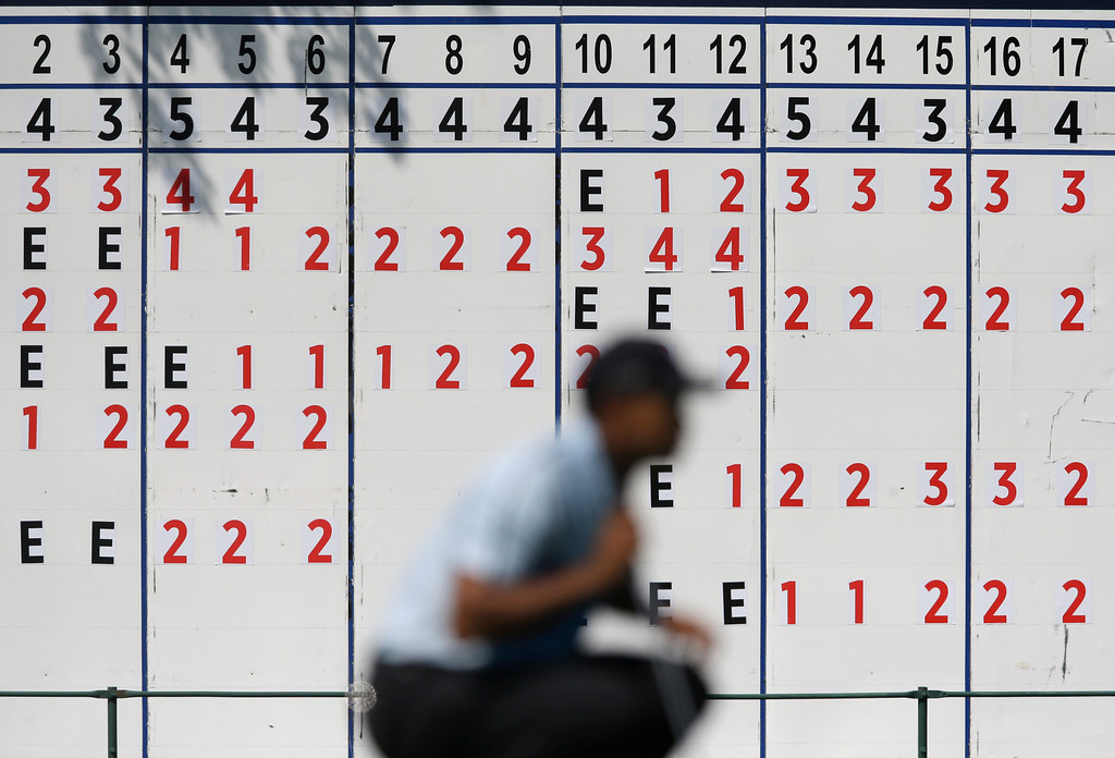 . Tiger Woods lines up a putt on the 18th hole near the leader board during the first round of the PGA Championship golf tournament at Oak Hill Country Club, Thursday, Aug. 8, 2013, in Pittsford, N.Y. (AP Photo/Patrick Semansky)