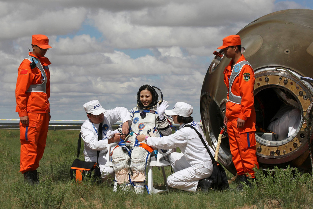 . Chinese astronaut Wang Yaping waves after she gets out from the re-entry capsule of China\'s Shenzhou-10 spacecraft returning to earth at its main landing site in north China\'s Inner Mongolia Autonomous Region, June 26, 2013. Three Chinese astronauts returned to Earth on Wednesday, touching down in north China\'s Inner Mongolia after a successful 15-day mission in which they docked with a manned space laboratory.  REUTERS/Stringer