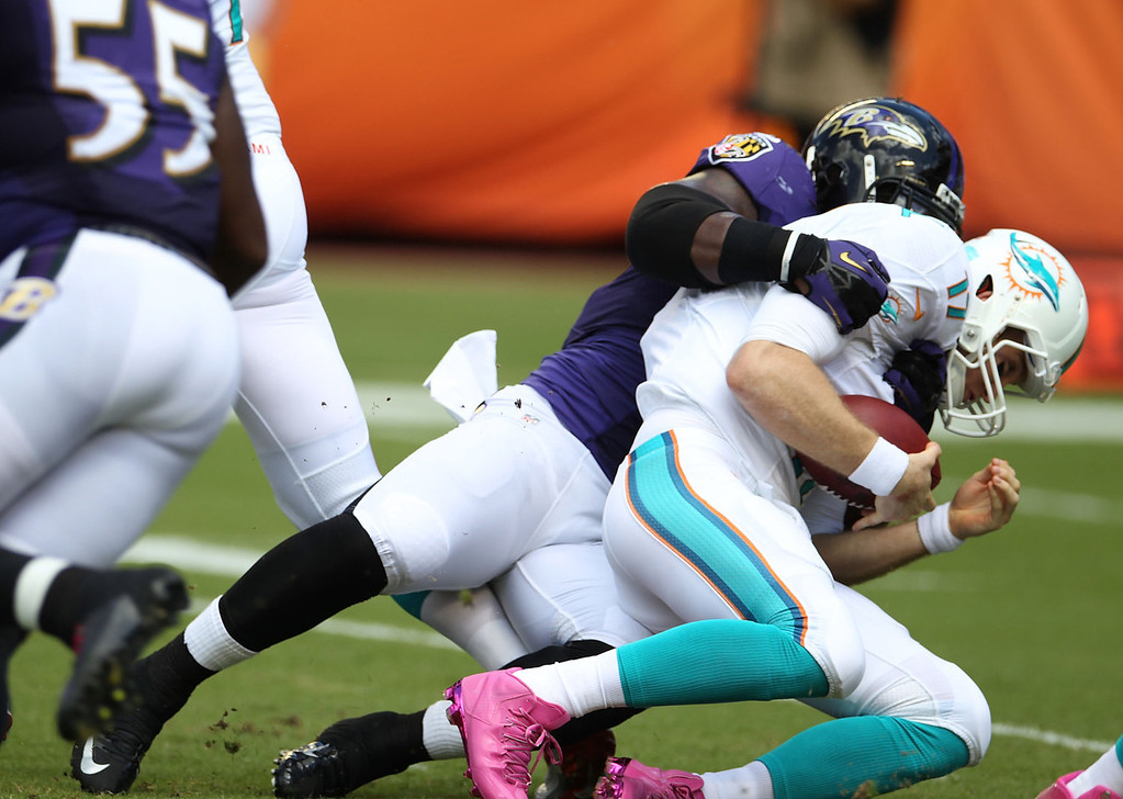 . Quarterback Ryan Tannehill #17 of the Miami Dolphins is sacked by Linebacker Daryl Smith #51 of the Baltimore Ravens at Sun Life Stadium on October 6, 2013 in Miami Gardens, Florida.  (Photo by Marc Serota/Getty Images)