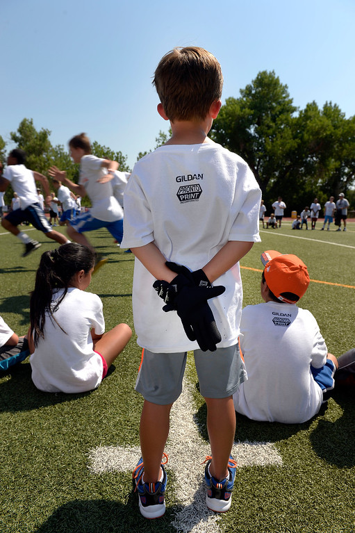. Jayden Reif 7, with his football gloves on watches the races from the sidelines during camp. Demaryius Thomas and Eric Decker team up with ProCamps for their football camp held at Littleton High School July 11, 2013. (Photo By John Leyba/The Denver Post)