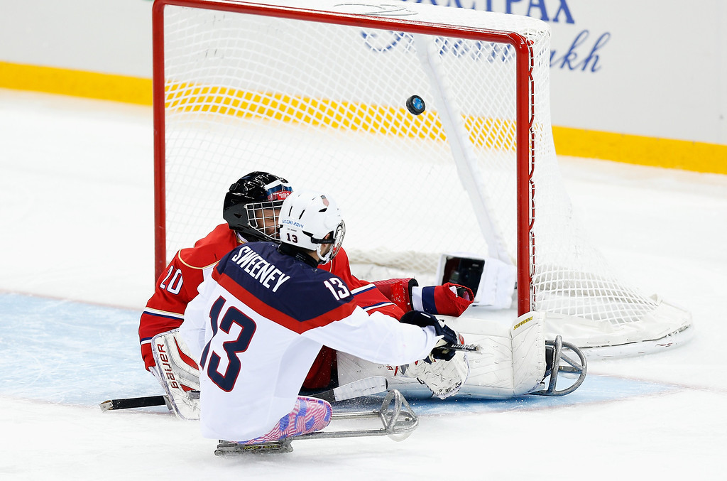 . Joshua Sweeney of USA scores his team\'s first goal past Russian goalkeeper Vladimir Kamantcev during the Ice Sledge Hockey Gold Medal match between Russia and USA at the Shayba Arena during day eight of the 2014 Paralympic Winter Games on March 15, 2014 in Sochi, Russia.  (Photo by Harry Engels/Getty Images)