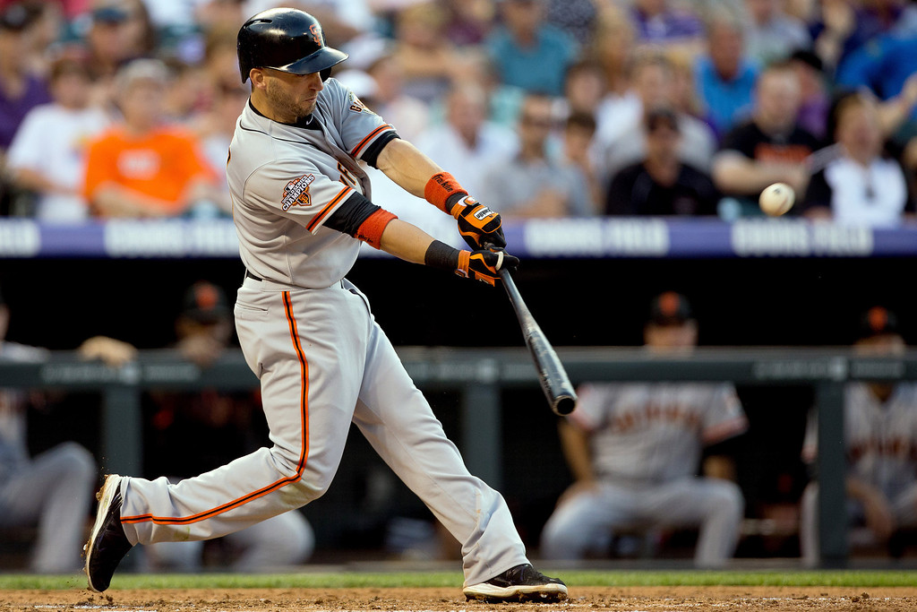 . DENVER, CO - MAY 17:  Marco Scutaro #19 of the San Francisco Giants hits an RBI single during the second inning against the Colorado Rockies at Coors Field on May 17, 2013 in Denver, Colorado.  (Photo by Justin Edmonds/Getty Images)