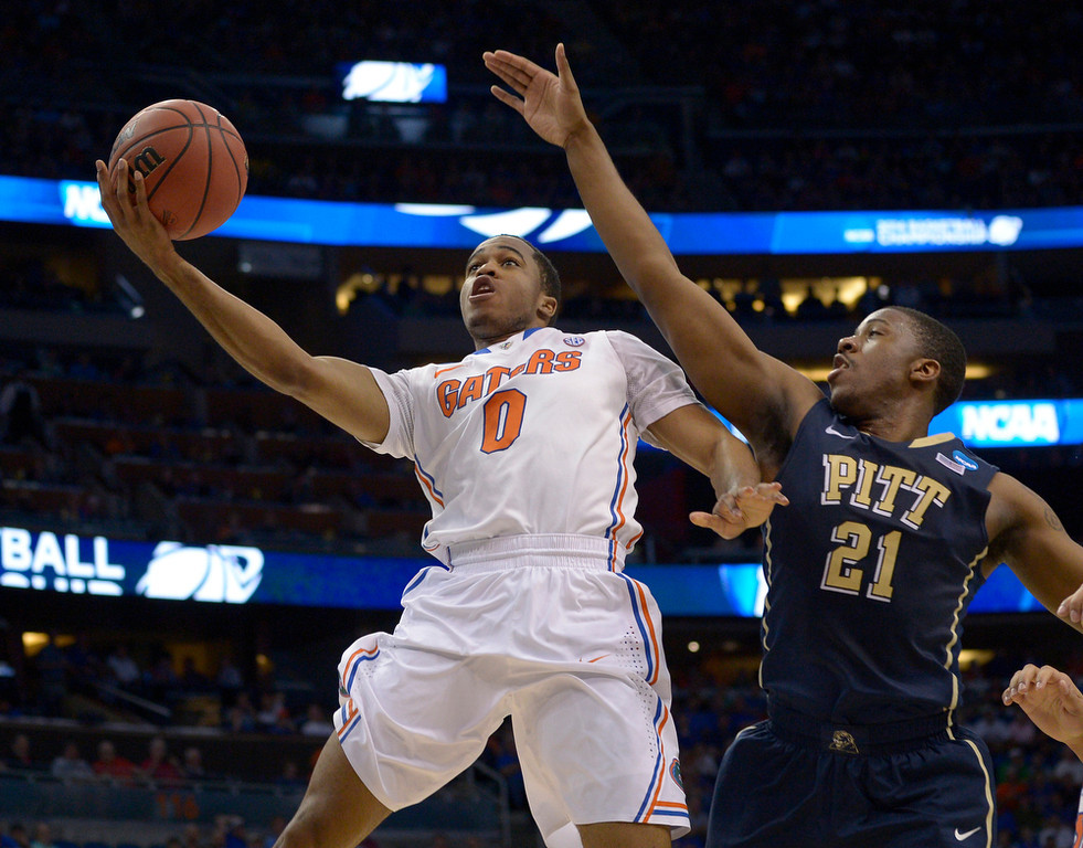 . Florida guard Kasey Hill (0) drives to the basket as Pittsburgh forward Lamar Patterson (21) defends during the first half in a third-round game in the NCAA college basketball tournament  Saturday, March 22, 2014, in Orlando, Fla. (AP Photo/Phelan M. Ebenhack)