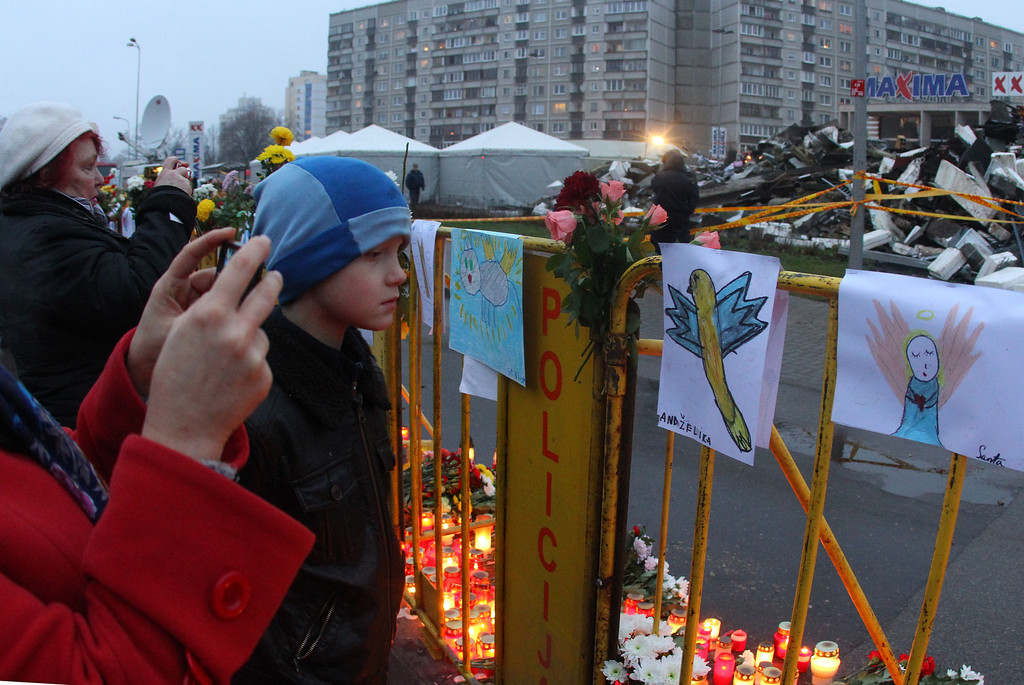 . People lay flowers and candles at the accident site of a collapsed Maxima supermarket in Riga on November 23, 2013, where the roof of the building caved in on shoppers on November 21.    AFP PHOTO / PETRAS MALUKAS/AFP/Getty Images