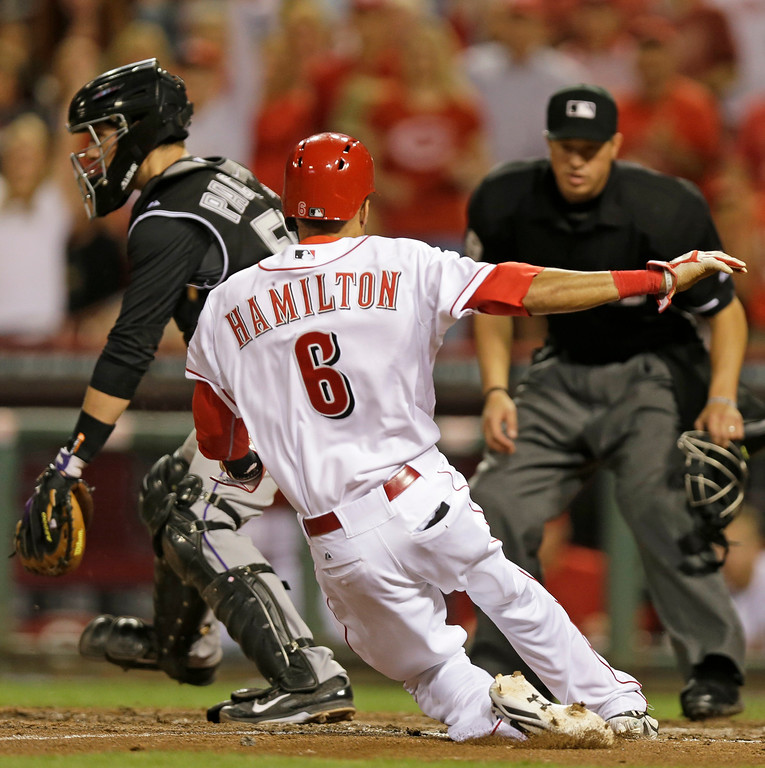 . Cincinnati Reds\' Billy Hamilton (6) scores on a sacrifice fly hit by Brayan Pena while Colorado Rockies catcher Jordan Pacheco waits for the throw in the eighth inning of a baseball game on Friday, May 9, 2014, in Cincinnati. Cincinnati won 4-3. (AP Photo/Al Behrman)