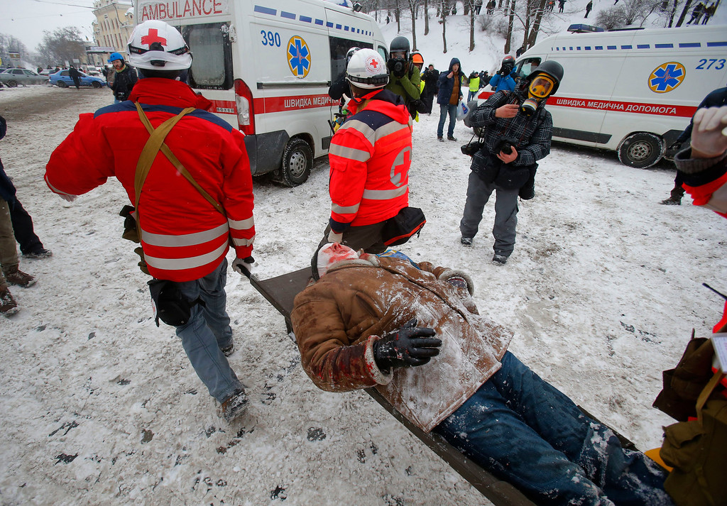 . Paramedics carry a wounded protestor on a stretcher away for clashes with police in central Kiev, Ukraine, Wednesday, Jan. 22, 2014. Police in Ukraine\'s capital on Wednesday tore down protester barricades and chased demonstrators away from the site of violent clashes, hours after two protesters died after being shot, the first violent deaths in protests that are likely to drastically escalate the political crisis that has gripped Ukraine since late November.  (AP Photo/Sergei Grits)