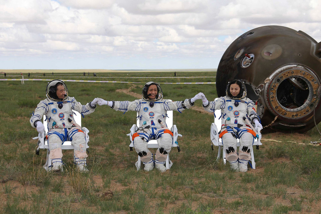. Astronauts Zhang Xiaoguang, Nie Haisheng and Wang Yaping, from left to right, join hands after they got out of the re-entry capsule of China\'s Shenzhou 10 spacecraft following its successful landing at the main landing site in Siziwang Banner, north China\'s Inner Mongolia Autonomous Region on Wednesday, June 26, 2013. The Chinese space capsule with three astronauts safely landed Wednesday on the country\'s northern grasslands after a 15-day trip to a prototype space station, marking the latest success for China\'s manned space program as it enters its second decade.  (AP Photo/Xinhua, Wang Jianmin)