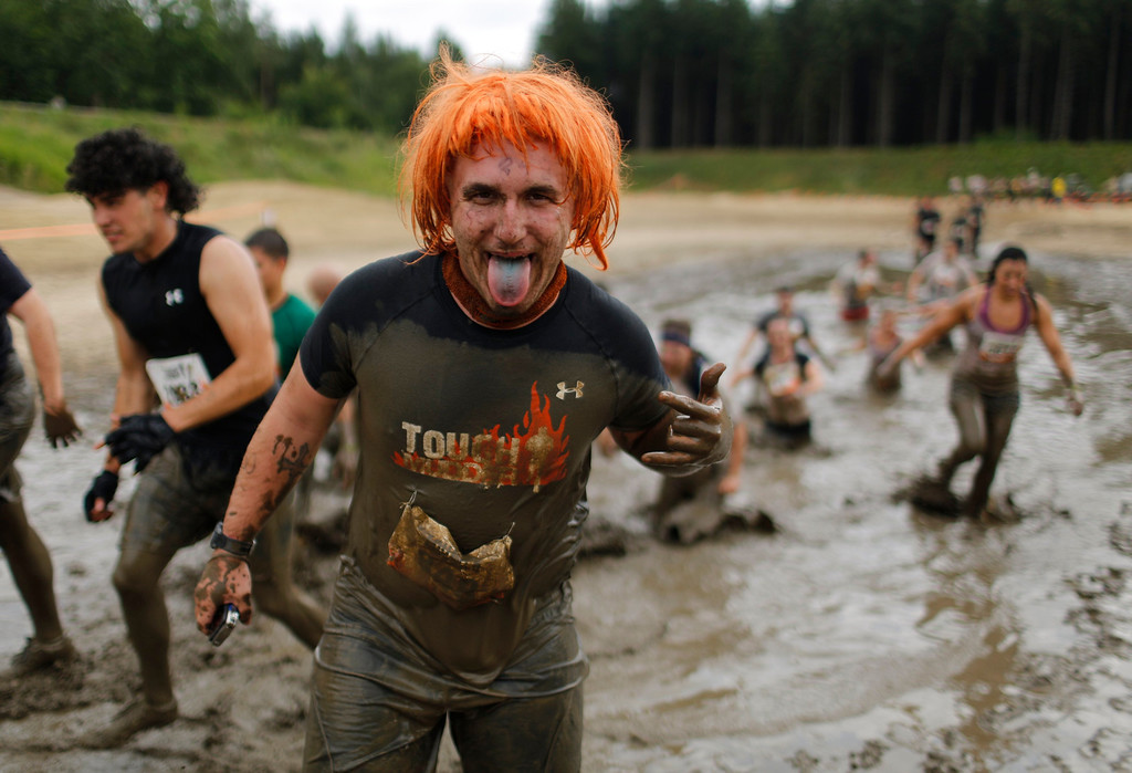 """. A participant of the \""""Tough Mudder\"""" endurance event series sticks out his tongue after passing the \""""Mud Mile\"""" obstacle in the Fursten Forest, a former British Army training ground near the north-western German city of Osnabrueck July 13, 2013. The hardcore but un-timed event over 16 km (10 miles) was designed by British Special Forces to test mental as well as physical strength. Some 4,000 competitors had to overcome obstacles of common human fears, such as fire, water, and heights.   REUTERS/Wolfgang Rattay"""