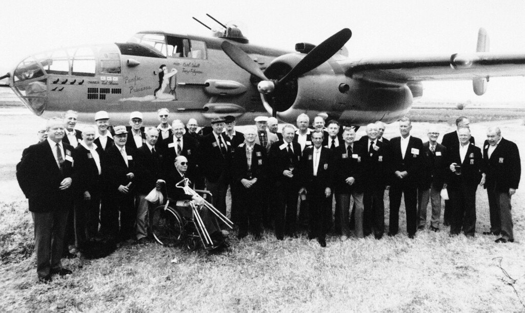 . FILE - In this April 17, 1987 file photo, thirty members of Jimmy Doolittle�s Tokyo Raiders pose for a group picture in front of a B-25J bomber in Torrance, Calif.,  as they gather for a reunion.   Thousands of visitors streamed to the national Air Force museum on Saturday, Nov. 9, 2013 to pay a Veterans Day weekend tribute to the few surviving members of the Doolittle Raiders, airmen whose daring raid on Japan helped boost American morale during World War II, as they planned to make their ceremonial final toast together.  Only four of the 80 Raiders are still living, and one was unable to attend because of health issues. (AP Photo/Douglas C. Pizac)