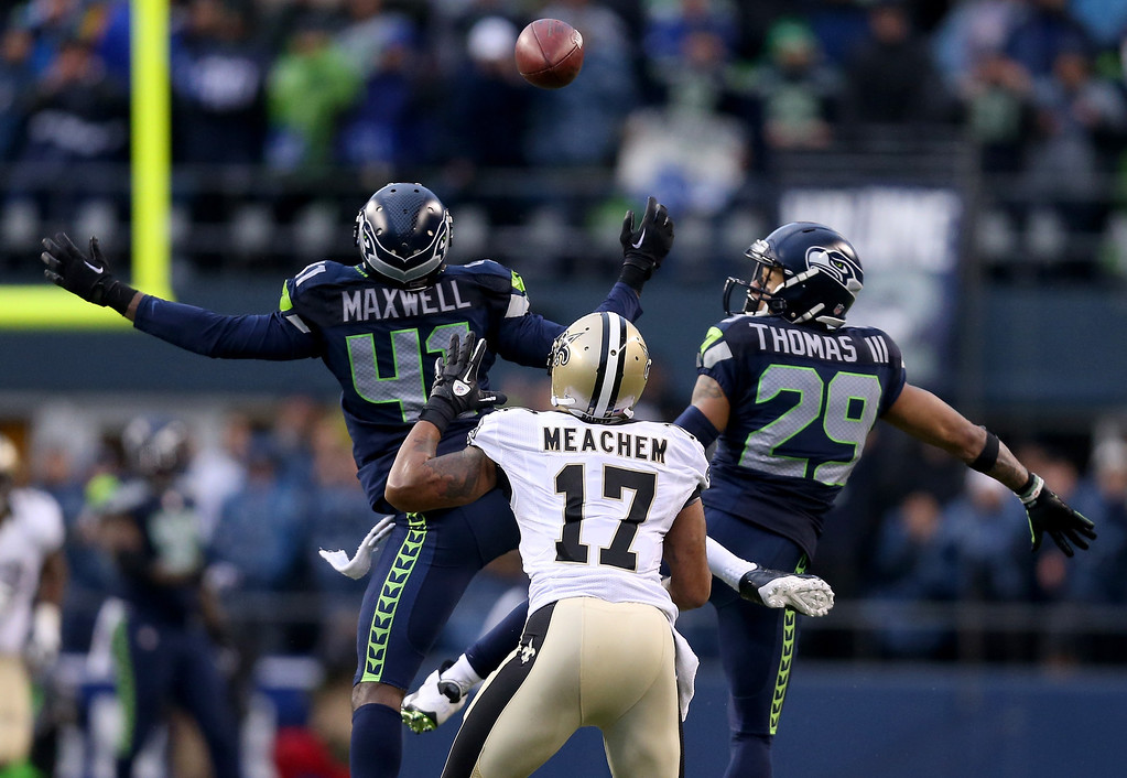 . SEATTLE, WA - JANUARY 11:  Cornerback Byron Maxwell #41 and free safety Earl Thomas #29 of the Seattle Seahawks are unable to make an interception as the ball is caught by wide receiver Robert Meachem #17 of the New Orleans Saints in the fourth quarter during the NFC Divisional Playoff Game at CenturyLink Field on January 11, 2014 in Seattle, Washington.  (Photo by Jeff Gross/Getty Images)