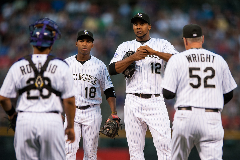 . DENVER, CO - AUGUST 31:  Juan Nicasio #12 of the Colorado Rockies is visited by pitching coach Jim Wright #52, Wilin Rosario #20, and Jonathan Herrera #18 in the first inning of a game against the Cincinnati Reds at Coors Field on August 31, 2013 in Denver, Colorado. The Rockies beat the Reds 9-6. (Photo by Dustin Bradford/Getty Images)